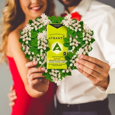 Couple holding Valentine's day heart with a box of Atrantil in it