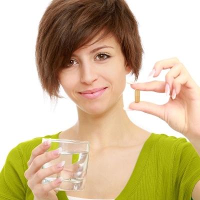 Woman holding Atrantil pill showing how to take Atrantil