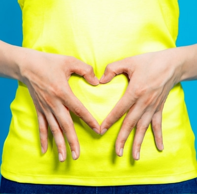 Woman with her hands in the shape of a heart over her stomach